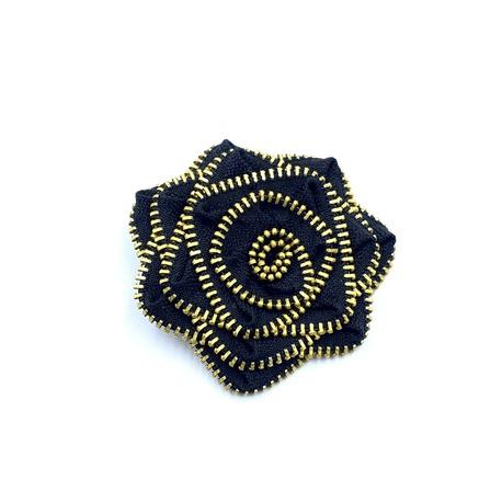 Ozdobna broszka do naszycia we wzór czarnego kwiata.
